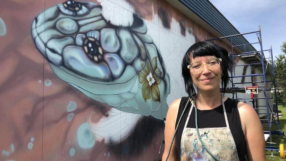 L'artiste pose devant une murale non complétée