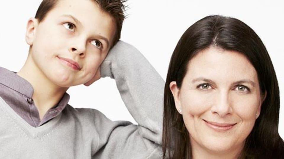 Un jeune garçon regarde vers le haut, appuyé sur son coude, alors que sa mère sourit et regarde la caméra.