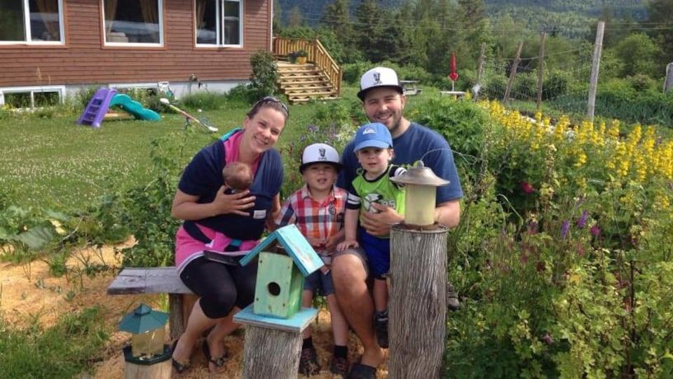 Caroline Michaud est assise dans son jardin aux côtés de son conjoint et de leurs trois enfants.