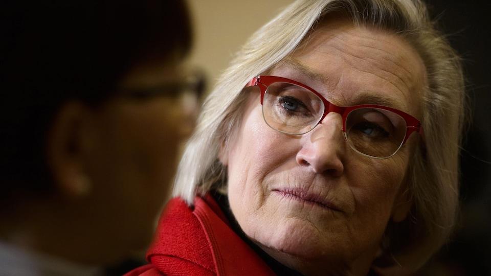 Une femme bonde aux lunettes rouges