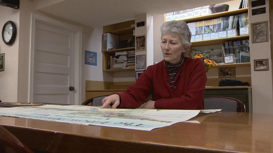 Carolyn Campbell assise à un bureau. Elle regarde une carte posée sur la table devant elle.