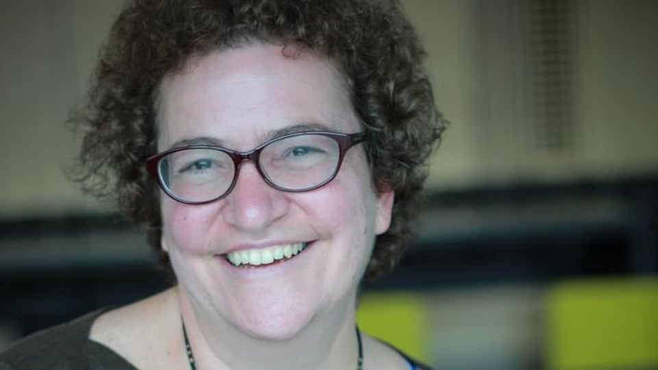 Une femme sourit à la caméra, photo professionnelle