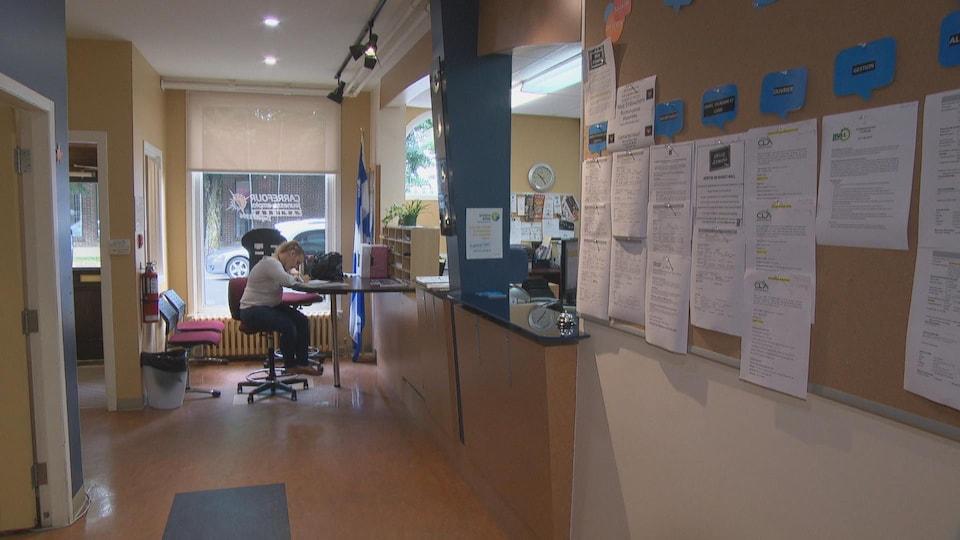 Une jeune femme rempli un formulaire. Un mur rempli d'offre d'emploi à droite.