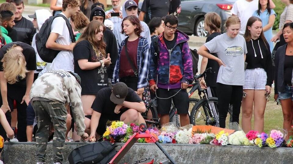 Des adolescents posent des fleurs sur le sol.