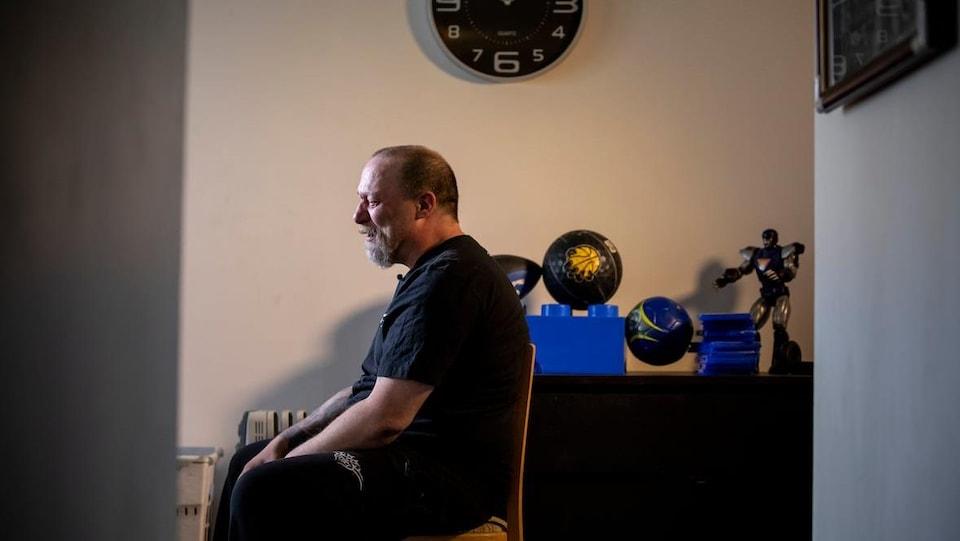 Plan large et de profil d'Aron Crimeni assis sur une chaise.