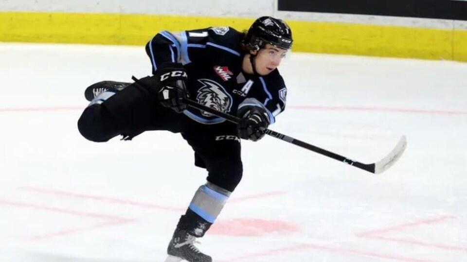 Le hockeyeur Carson Lambos fait une passe à un coéquiper. Il est seul sur la photo.