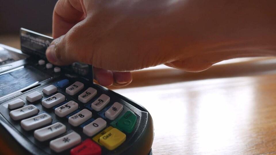 Gros plan sur quelqu'un qui passe sa carte de crédit dans un terminal de paiement électronique.