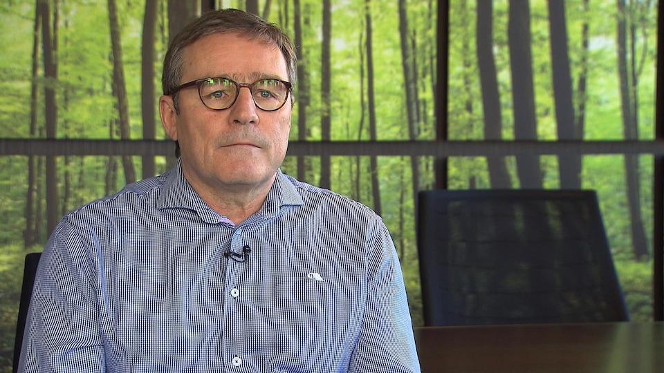 Un homme portant des lunettes est assis dans une salle de conférence devant un mur sur lequel des photographies d'arbres sont accrochées.