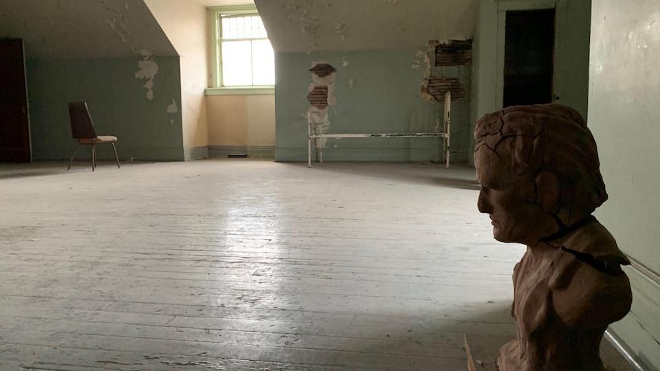 Un buste délabré laissé sur le plancher d'une salle.