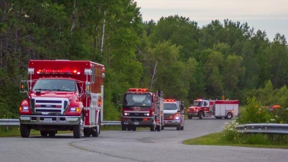 Des camions de pompiers défilent dans une rue rurale.