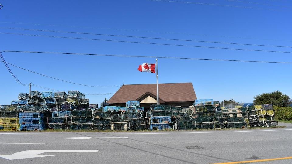 Des casiers à homard empilés devant les bureaux de Pêches et Océans Canada à Meteghan.