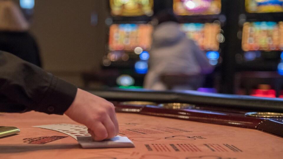 Une main manipule des cartes sur une table de jeu.