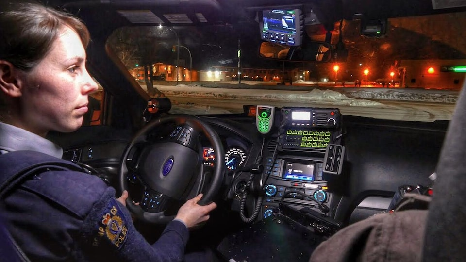 Une policière à l'intérieur de son véhicule lors d'une patrouille du vendredi soir.
