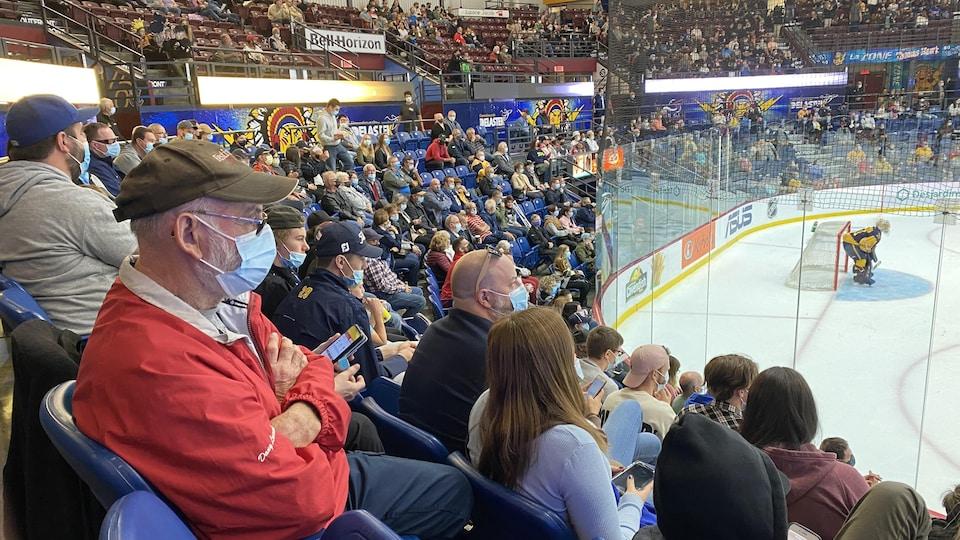De nombreux spectateurs portant le masque assistent à une partie de hockey des Cataractes de Shawinigan.