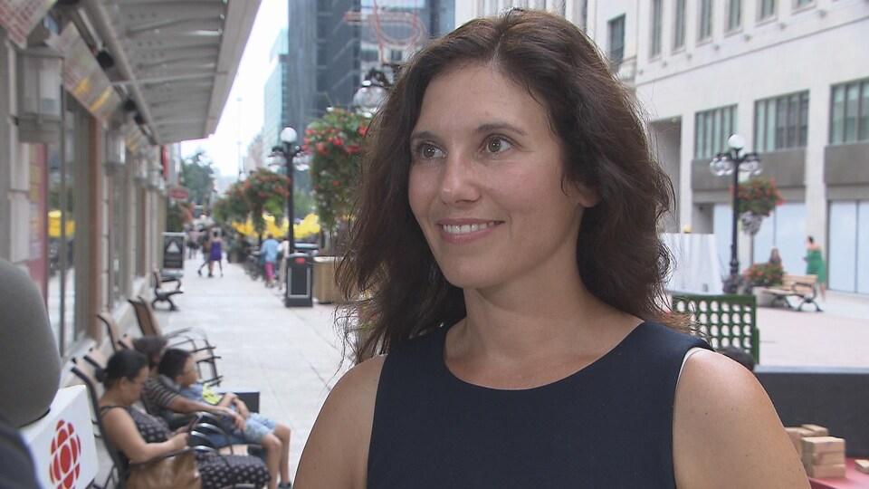 Catherine Callary est souriante et parle au micro lors d'une entrevue rue Sparks