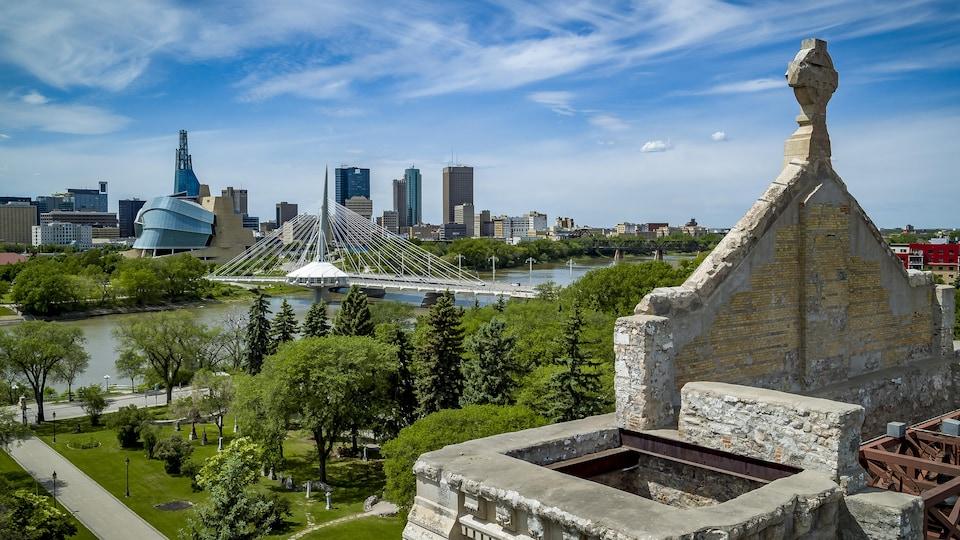 Une vue aérienne depuis les murs de pierre de l'ancienne cathédrale de Saint-Boniface, où l'on voit l'esplanade Louis-Riel, le pont Provencher, le Musée canadien pour les Droits de la personne et les immeubles de Winnipeg.