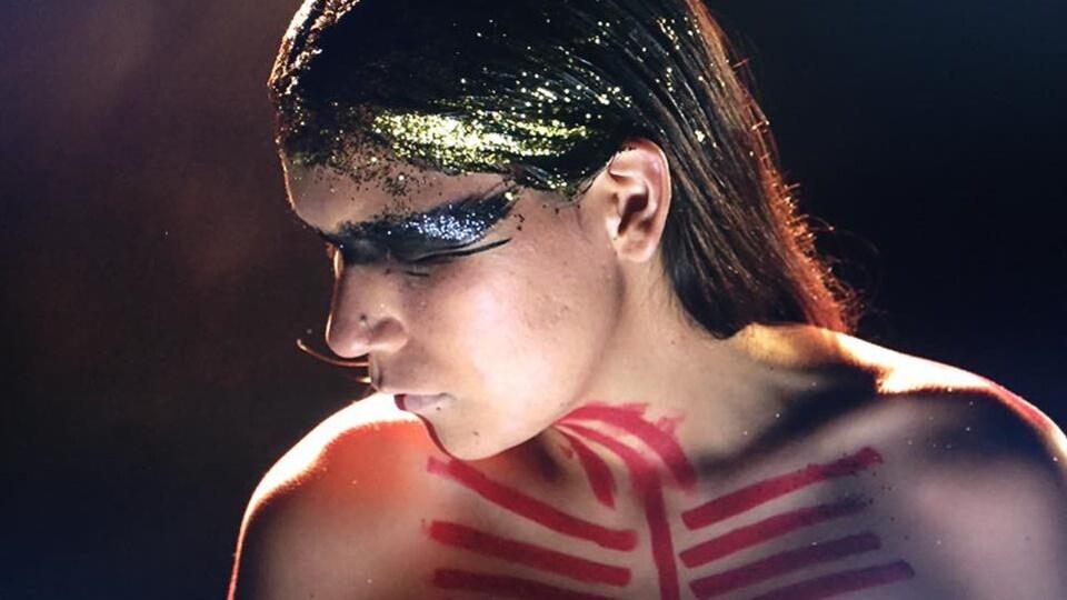 Une Atikamekw est peinte de symboles tribaux et a des paillettes dorées dans ses cheveux.