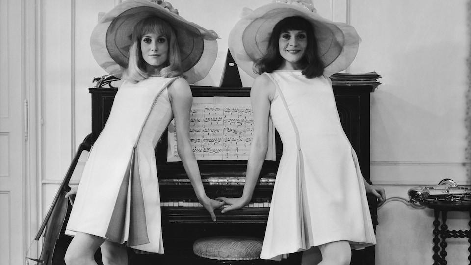 Les deux femmes portent de grands chapeaux et posent devant un piano.