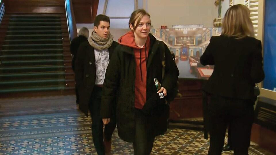 Catherine Dorion porte un coton ouaté orange qu'on aperçoit sous un manteau noir.