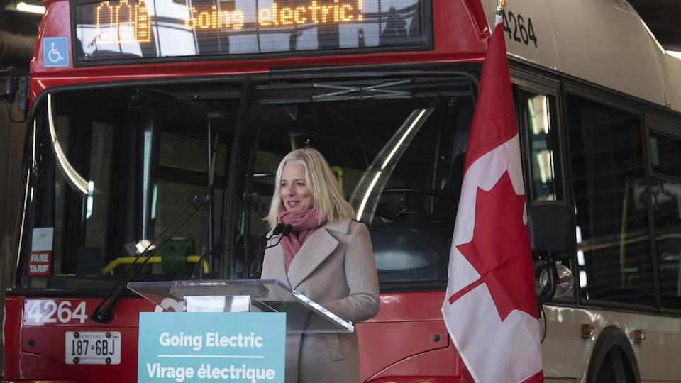 Catherine McKenna devant un autobus et un drapeau canadien. Elle parle devant un lutrin sur lequel une pancarte dit : Virage électrique.