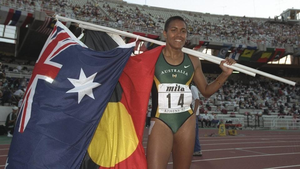 L'athlète pose pour les photographes avec le drapeau aborigène et le drapeau australien.