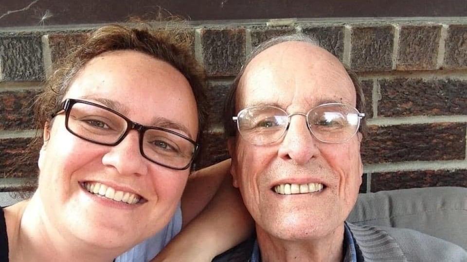Une femme et un homme plus âgé, souriants, devant un mur de briques.
