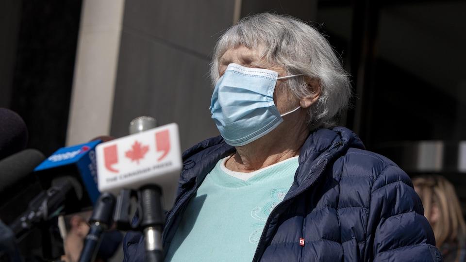 Cathy Riddell porte un masque et parle dans des micros placés devant elle.