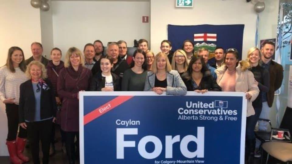 Laureen Harper et une partie de l'équipe de campagne pose pour la photo derrière une pancarte de soutien à Caylan Ford