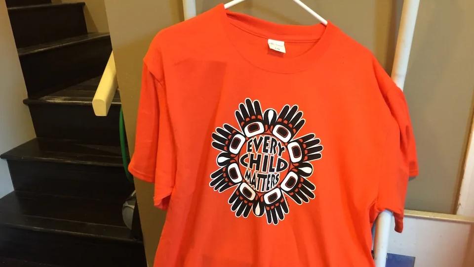 Un chandail orange portant l'inscription, en anglais, «tous les enfants comptent», est suspendu à côté d'un escalier.