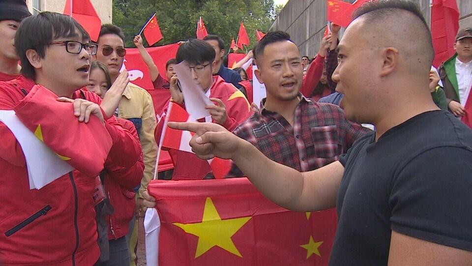 Un homme en pointe un autre devant une foule aux couleurs du drapeau chinois.