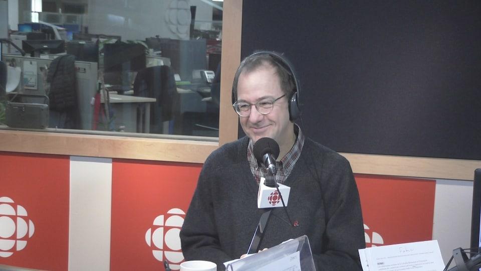 Alain Fortier, un homme portant des lunettes, est assis dans un studio de radio, devant un microphone, avec des écouteurs sur la tête.