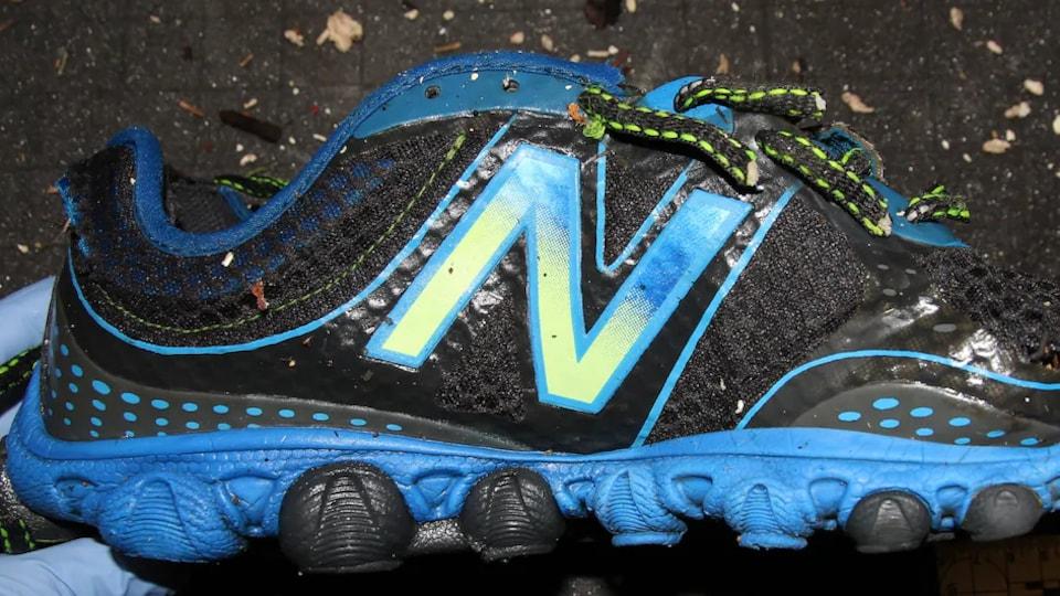 Une main recouverte d'un gant de latex tient une chaussure bleu et noir arborant la lettre N.