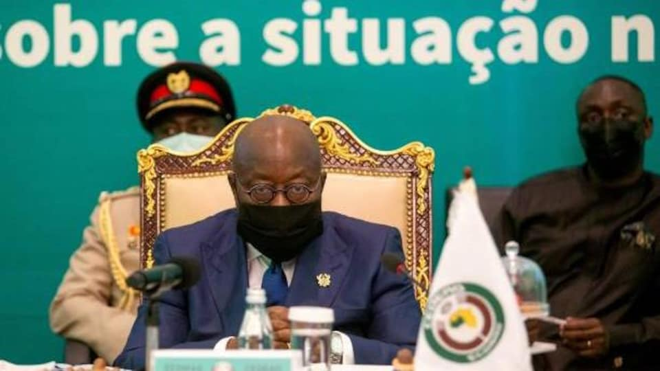 Un homme masqué assis à table préside une réunion.