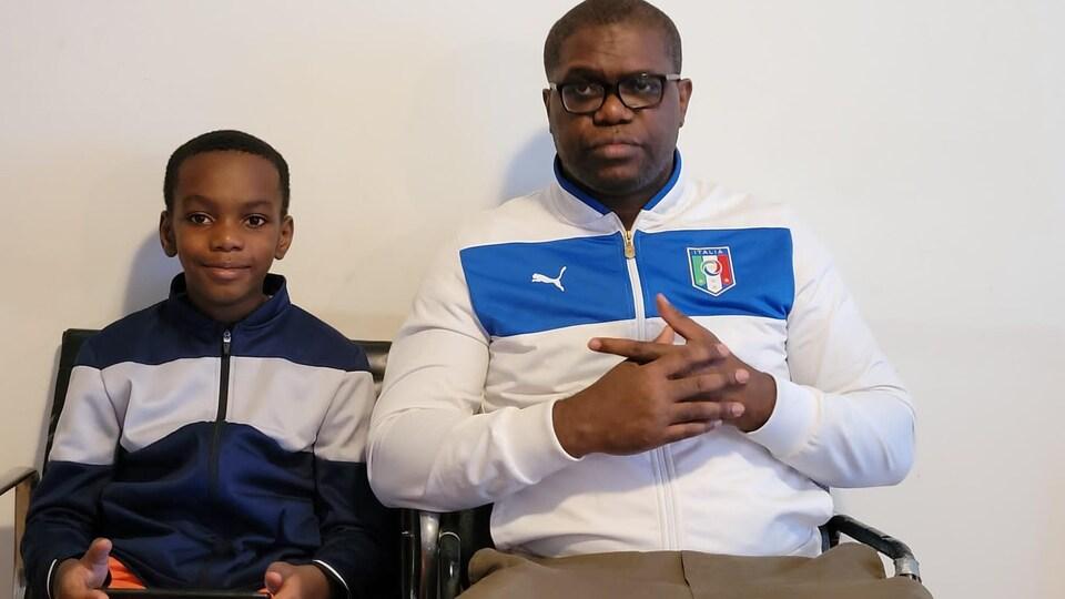 Cédric Engoné et Enzo Noah Engone assis devant un mur blanc.