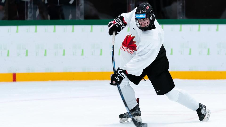 Un joueur de hockey qui s'entraîne avec un chandail blanc de l'équipe canadienne de hockey.