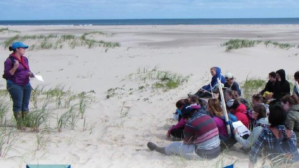 Un groupe de gens assis dans les dunes aux Îles-de-la-Madeleine.