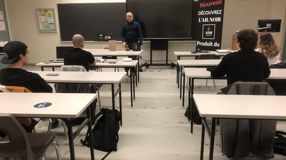 Un homme parle devant une classe