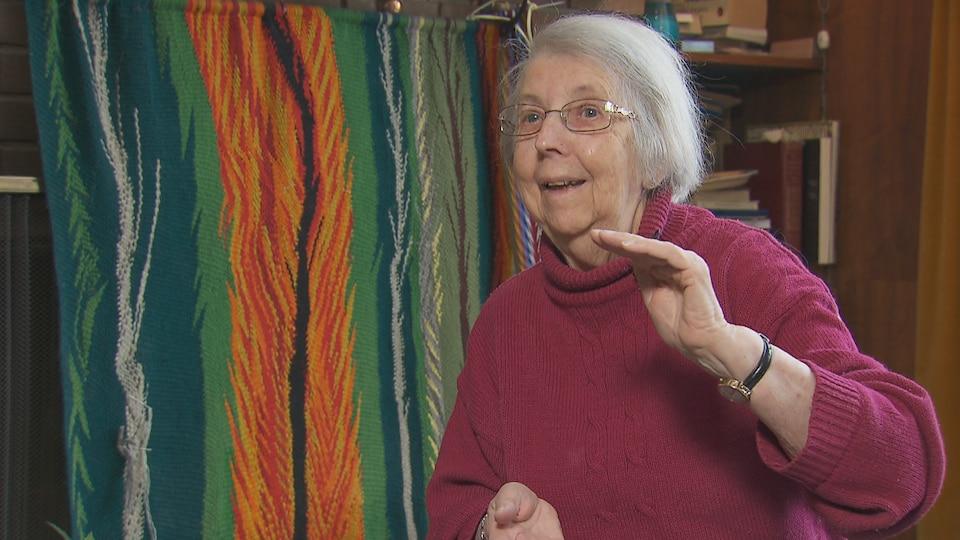 Une dame âgée assise dans une salle devant une ceinture fléchée dans l'arrière-plan.