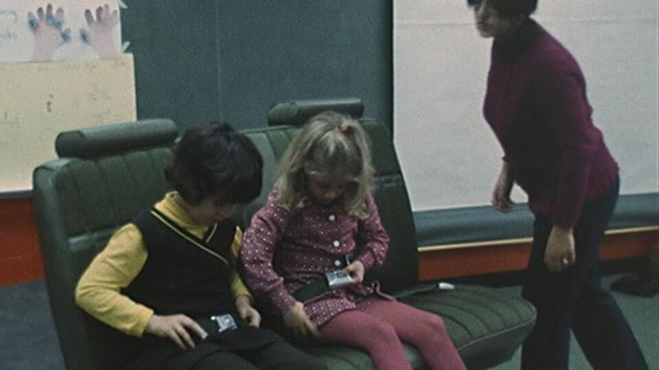 Une professeure observe deux élèves boucler leur ceinture de sécurité sur un banc de voiture placé dans une classe d'école.
