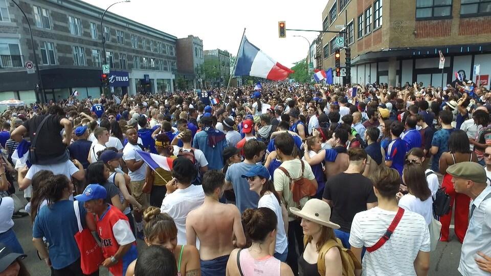 Une foule avec des drapeaux bleu-blanc-rouge massée sur la rue Saint-Denis