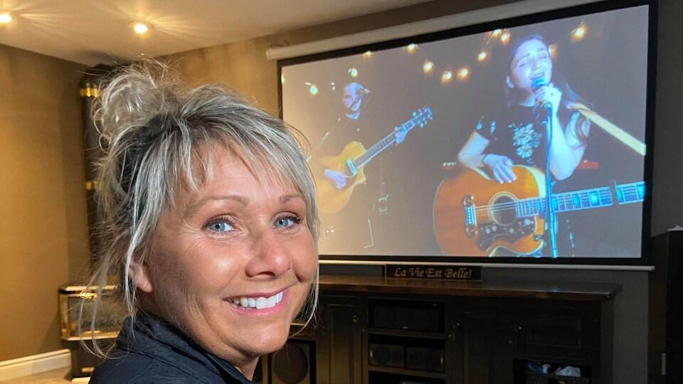 Une femme écoute le concert de Céleste sur sa télé.
