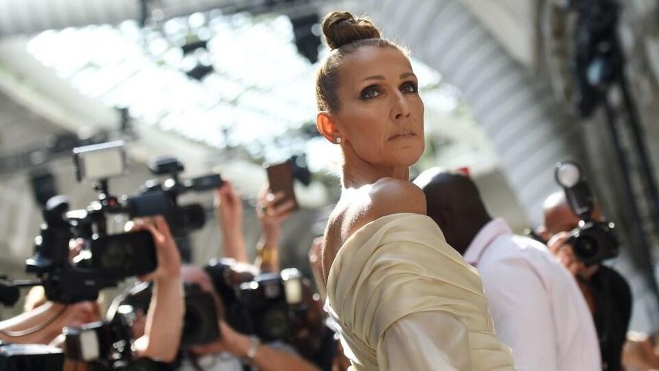Céline Dion est entourée de photographes.