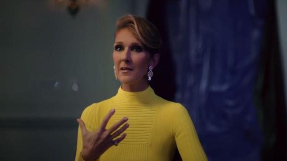 La femme a les cheveux remontés et porte une robe jaune.