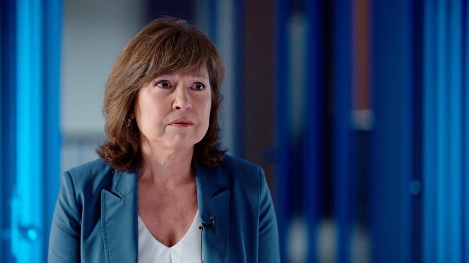 Une femme, vêtue d'un veston bleu, regarde dans le vide, les larmes aux yeux.