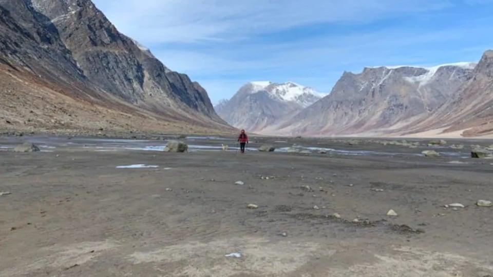 Céline Jaccard entourée de montagnes sur le col Akshayuk sous un ciel légèrement nuageux.