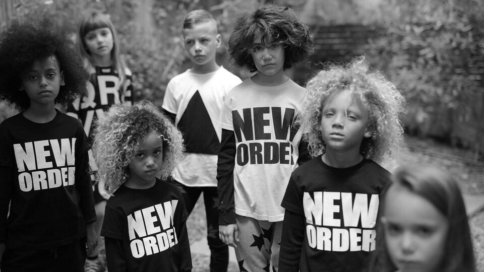 Plusieurs enfants de différents âges posent avec des vêtements sur lesquels est écrit New order.