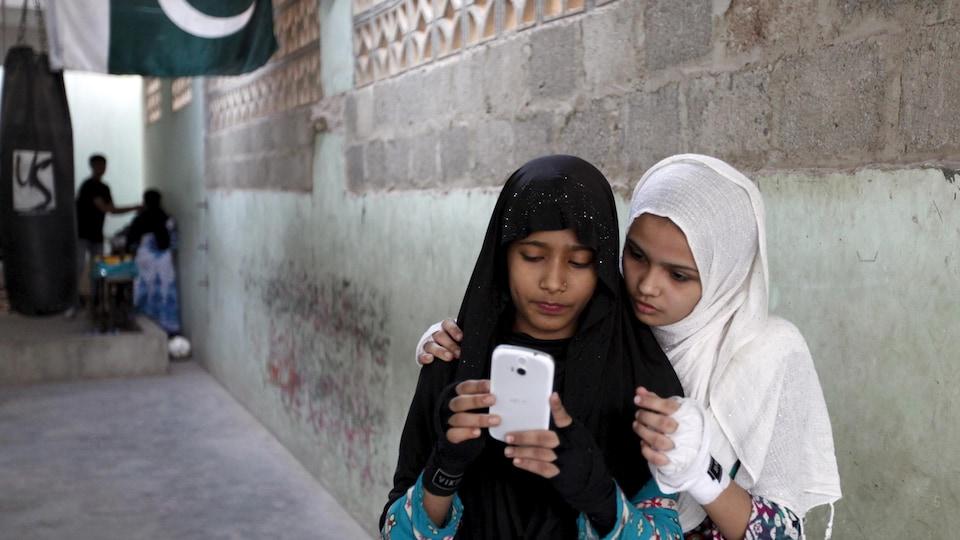 Deux jeunes Pakistanaises portant le voile regardent le même téléphone cellulaire blanc.
