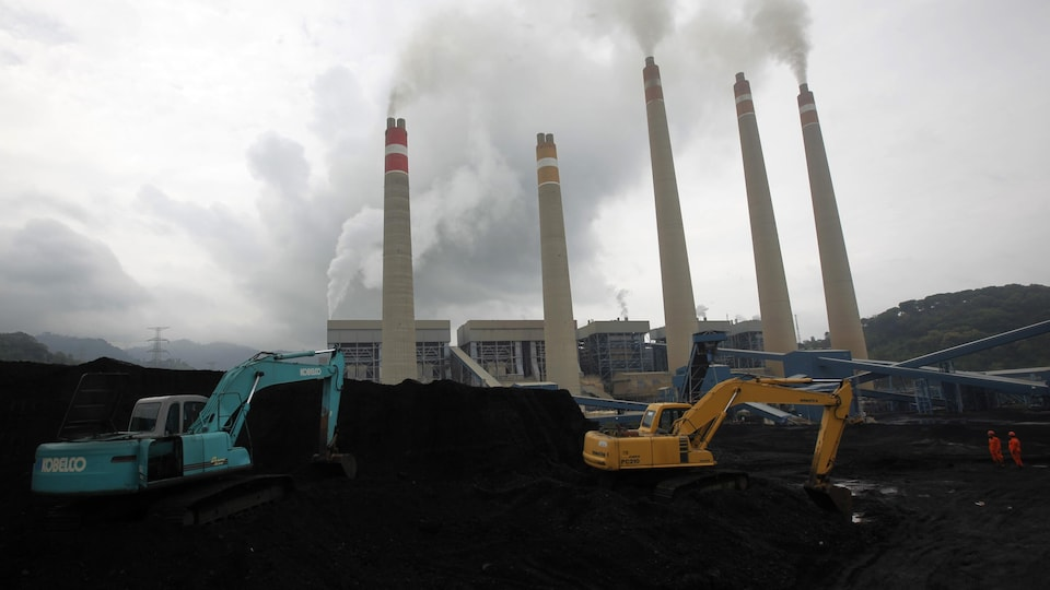 Les excavatrices sont devant des cheminées qui exhalent de la fumée.