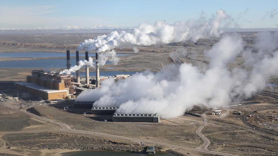 Un paysage désertique avec, au centre, une centrale camouflée dans une épaisse fumée blanche