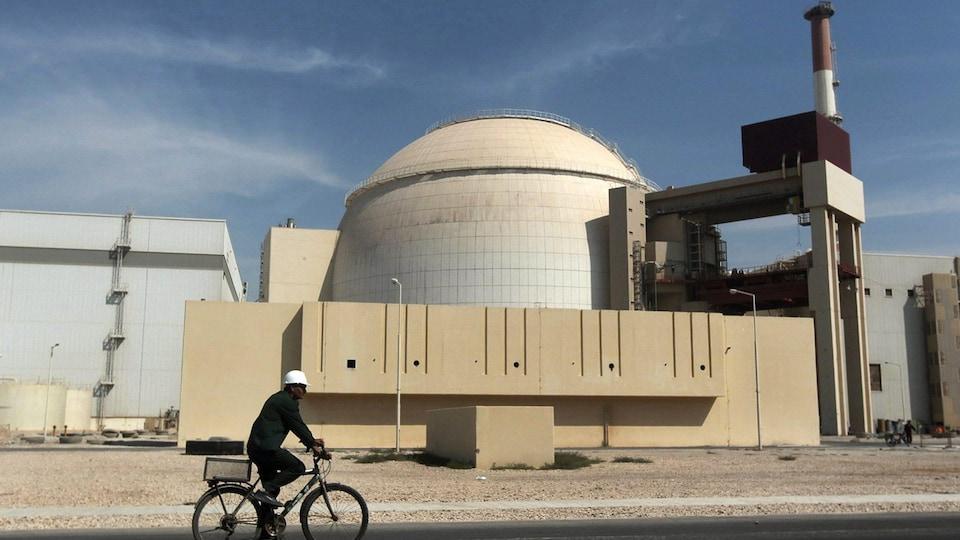 Un cycliste passe devant les installations d'une centrale nucléaire.